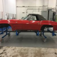 red corvette on rotisserie for disassembly