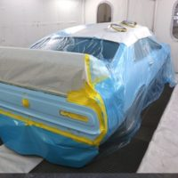 car prepped for paint within paint booth